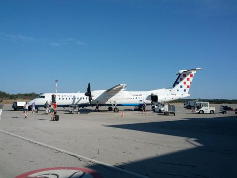 Airplane of the Croatian Airlines in the airport in Pula while passengers boarding